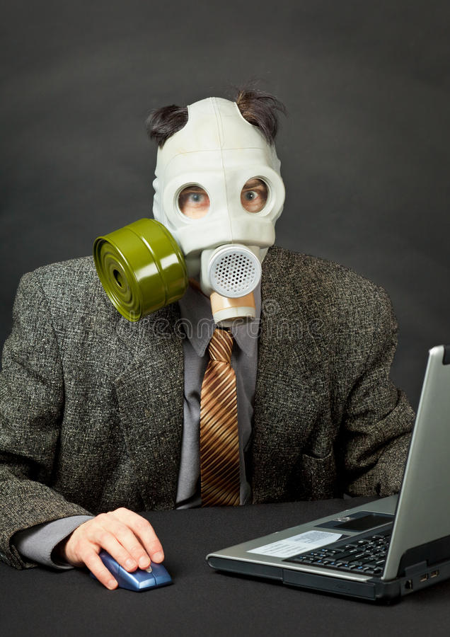 Download Amusing Person In Gas Mask Works With Computer Stock Image - Image: 15628197
