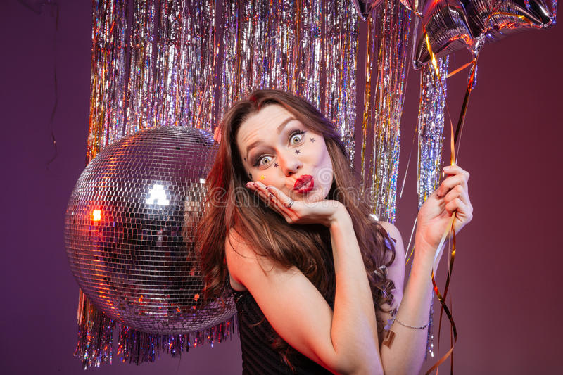 Amusing pretty woman holding balloon and sending a kiss royalty free stock images
