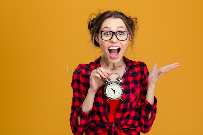 Amusing pretty young woman holding alarm clock and shouting stock images