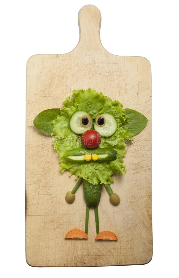 Amusing vegetable monster made on cutting board. Funny monster made with salad, cucumber and carrot. Creative idea to make a fantasy creature with simple food stock images