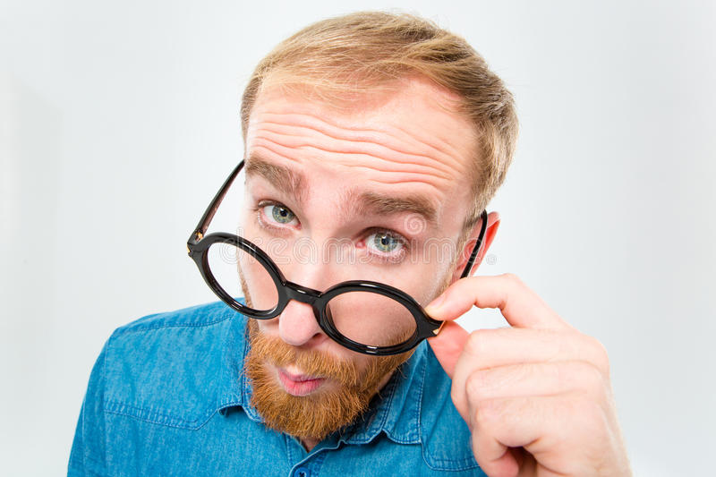 Amusing young man with beard looking over black round glasses. Closeup portrait of amusing young man with beard looking over black round glasses over white stock image