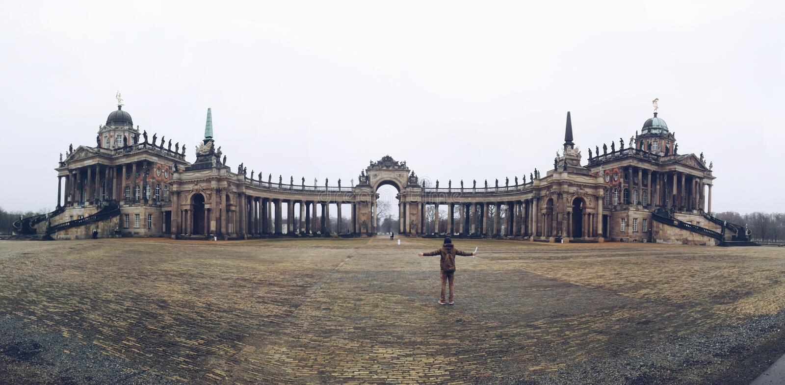 The amuzing contrast between the huge and the small. In this picture we can see the old gate of Potsdam University, Germany. It is located next to the stock images
