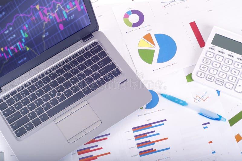 Análise de dados - local de trabalho com gráficos e cartas de negócio, portátil e calculadora imagens de stock
