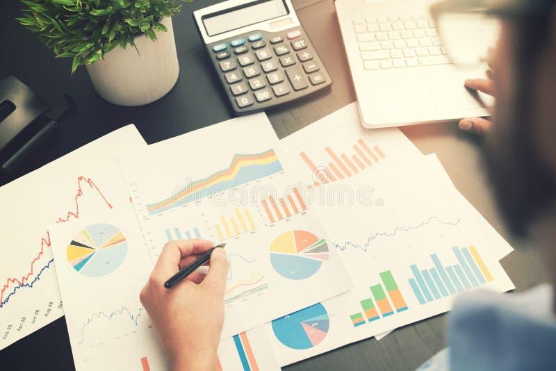 Análise de negócio - equipe o trabalho com cartas dos dados financeiros imagem de stock
