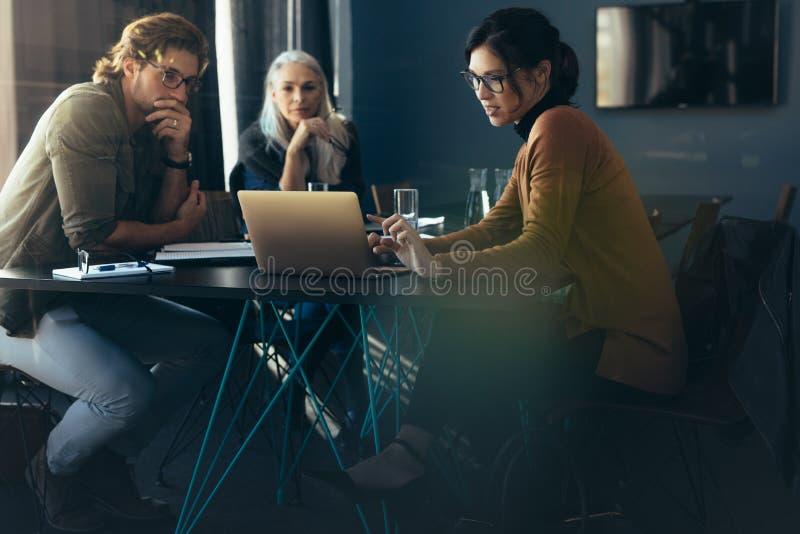 Análise do projeto da exibição da mulher de negócios aos colegas fotos de stock royalty free