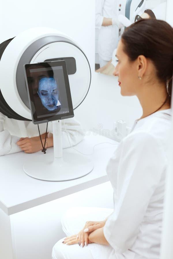Análisis de la piel de la cara Mujer en la cosmetología que hace diagnóstico de la piel imagenes de archivo
