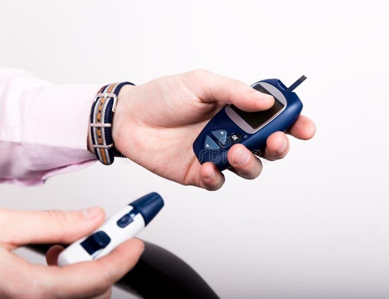 Análisis de sangre llano de medición de la glucosa usando glucometer ultra mini y la pequeña gota de la sangre de tiras del finge imagen de archivo libre de regalías