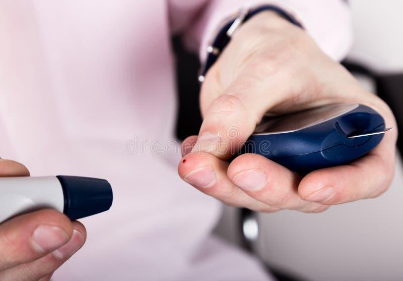Análisis de sangre llano de medición de la glucosa usando glucometer ultra mini y la pequeña gota de la sangre de tiras del finge imágenes de archivo libres de regalías