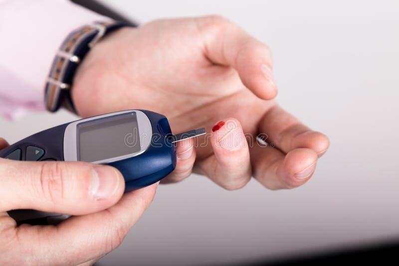 Análisis de sangre llano de medición de la glucosa usando glucometer ultra mini y la pequeña gota de la sangre de tiras del finge fotos de archivo libres de regalías