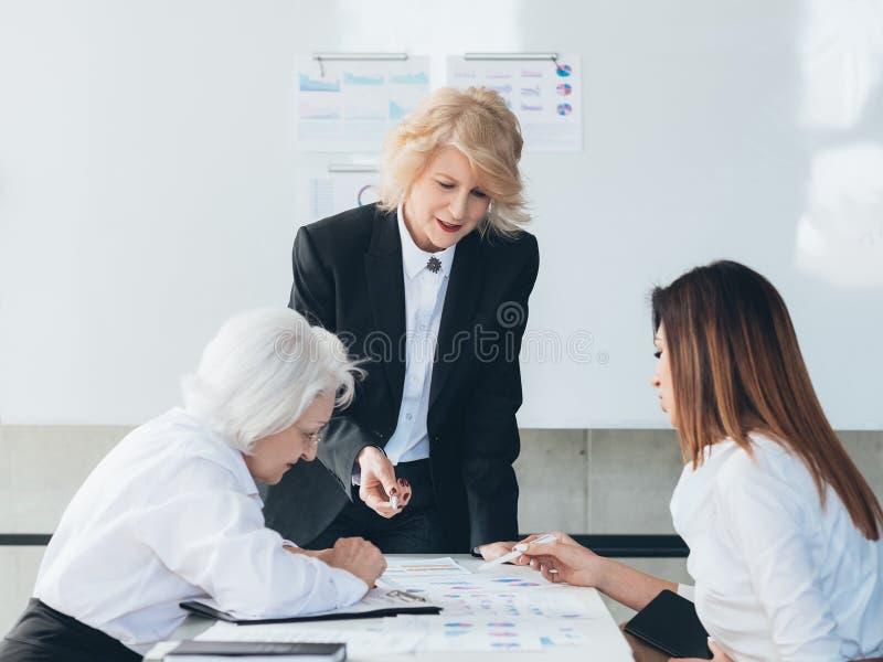 An?lisis del infographics de las mujeres de negocios de la reuni?n del equipo fotos de archivo libres de regalías