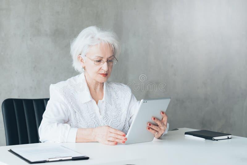 Análisis digital del negocio de la tableta confiada de la señora fotografía de archivo