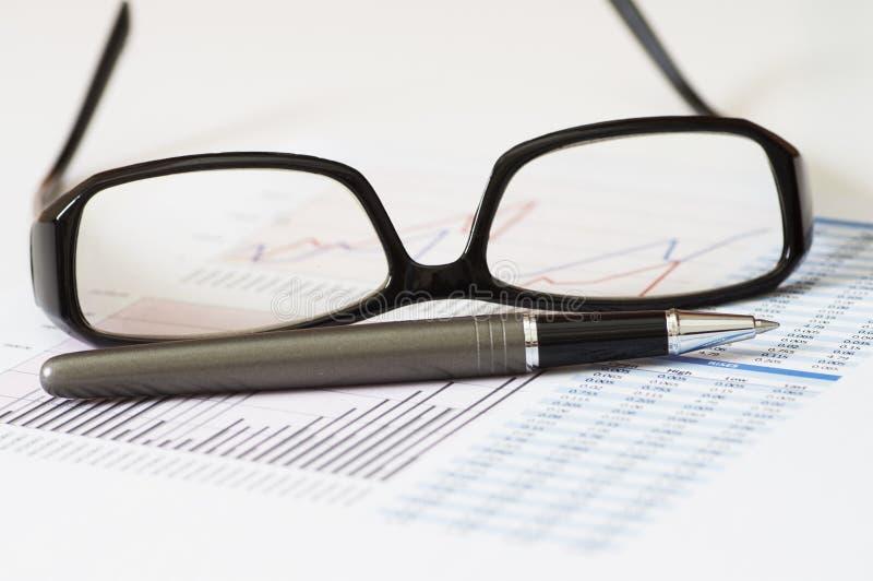 Análisis e informe de negocio con la pluma, los vidrios y la carta fotos de archivo