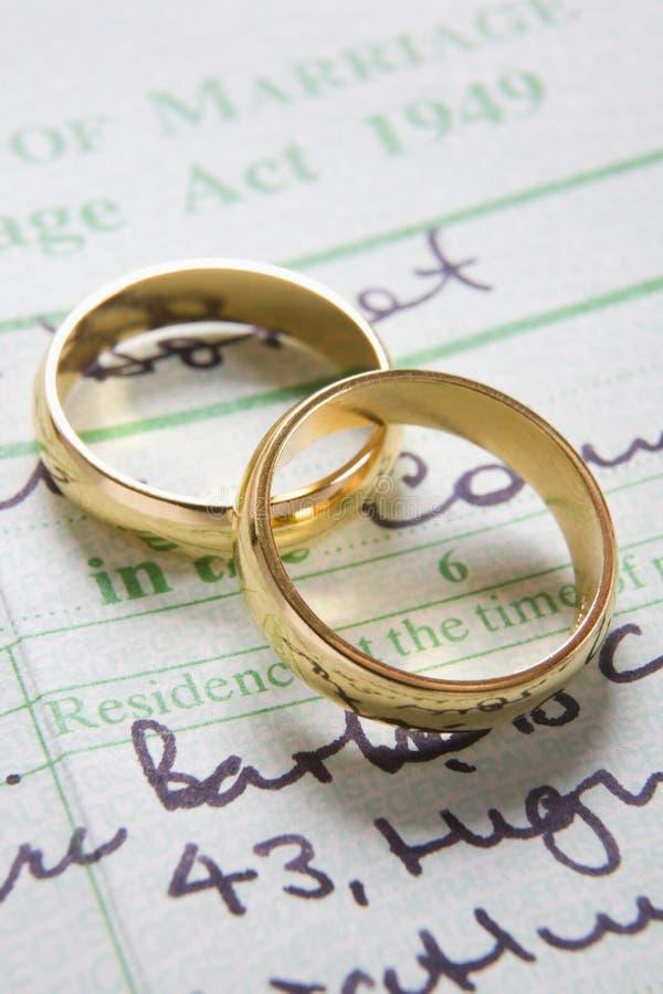 Anéis de casamento do ouro no certificado de união imagem de stock