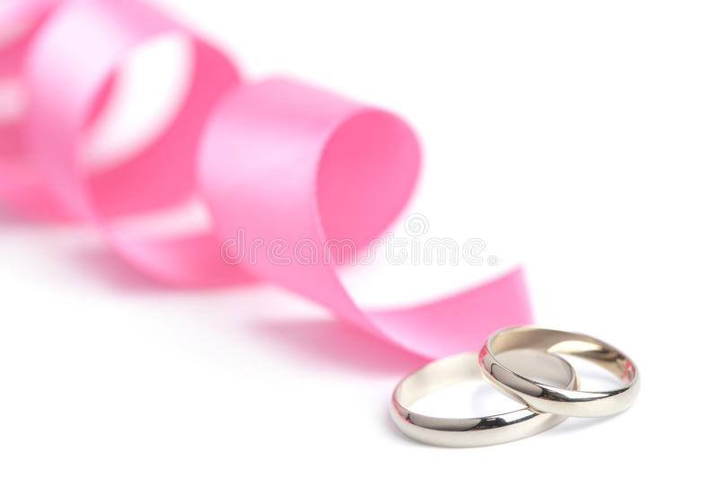 Anéis de casamento e fita cor-de-rosa isolados imagem de stock royalty free