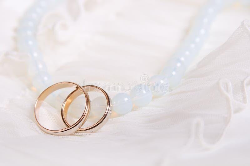 Anéis de casamento e grânulos azuis fotos de stock