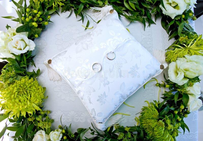 Anéis de casamento em um coxim branco em uma grinalda das flores foto de stock royalty free