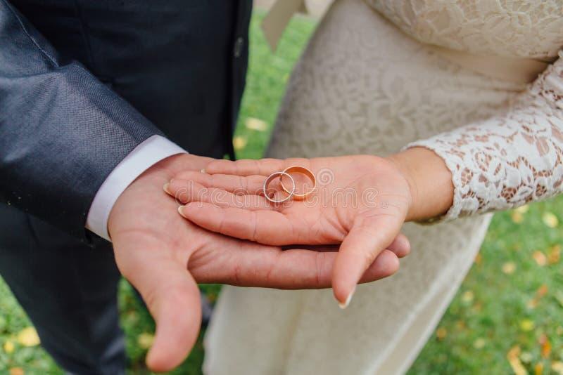 Anéis de casamento nas mãos fotografia de stock royalty free