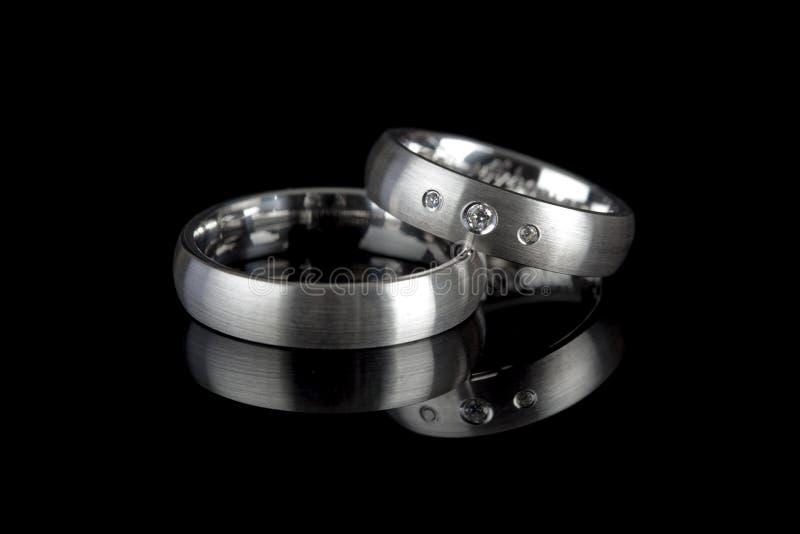 Anéis de casamento no fundo preto imagem de stock