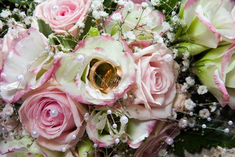 Anéis de casamento no ramalhete da noiva fotografia de stock royalty free