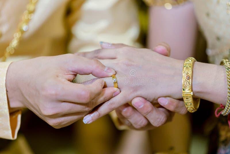 Anéis de casamento Pôs a aliança de casamento sobre ela Feche acima do noivo Put o anel na noiva Cerimónia de casamento tailandes imagens de stock