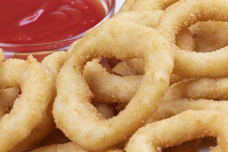 Anéis de cebola deliciosos e ketchup em uma placa imagens de stock