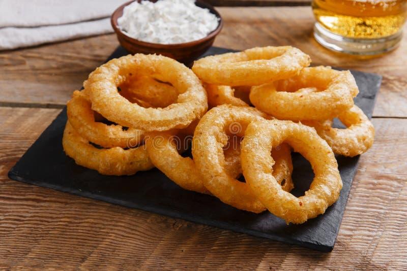 Anéis de cebola fritados na massa com molho fotografia de stock royalty free