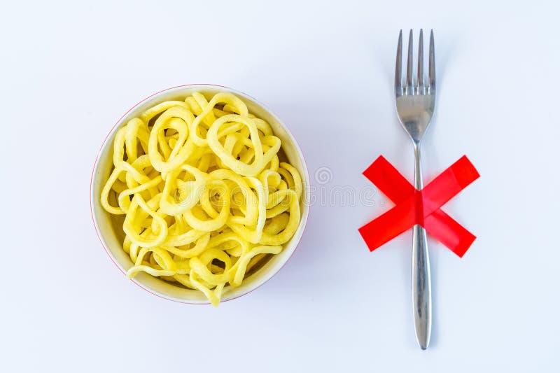 Anéis de cebola na placa com a forquilha com cruz vermelha de X na tabela Fazendo dieta, conceito insalubre do estilo de vida imagem de stock royalty free