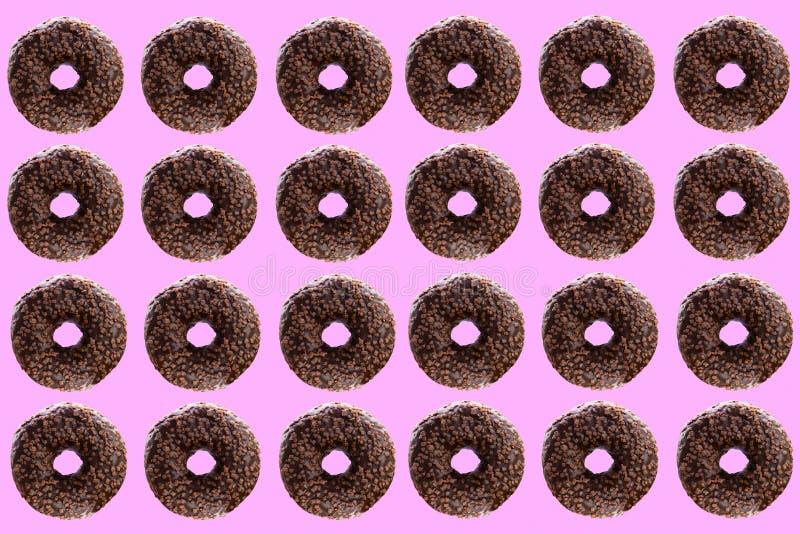Anéis de espuma do chocolate em um fundo cor-de-rosa fotos de stock