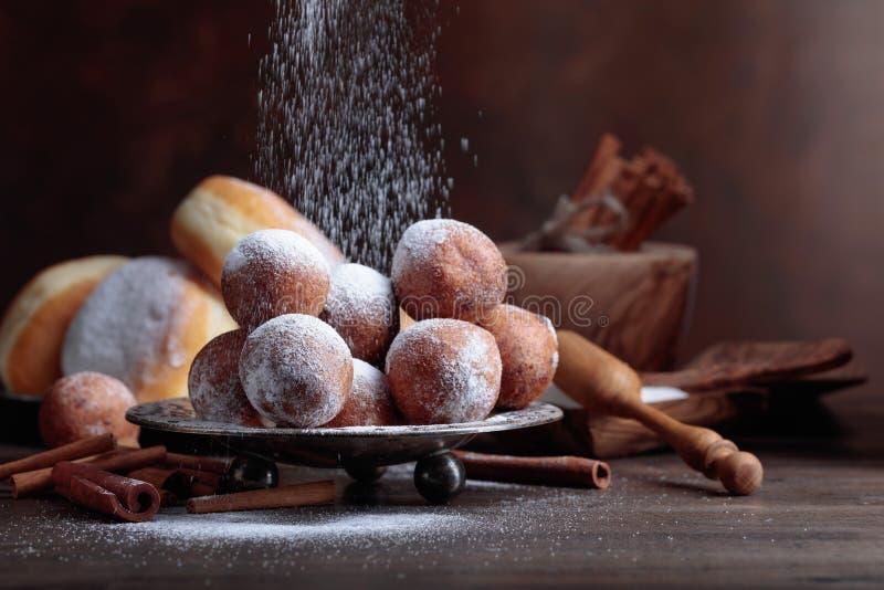Anéis de espuma doces com as varas de canela pulverizadas com açúcar imagens de stock royalty free