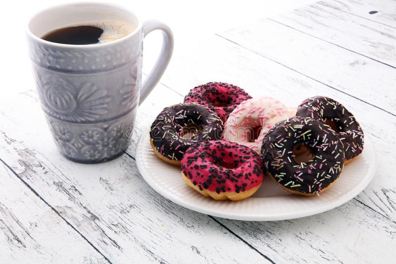 Anéis de espuma e café para um café da manhã doce no fundo de madeira fotos de stock royalty free