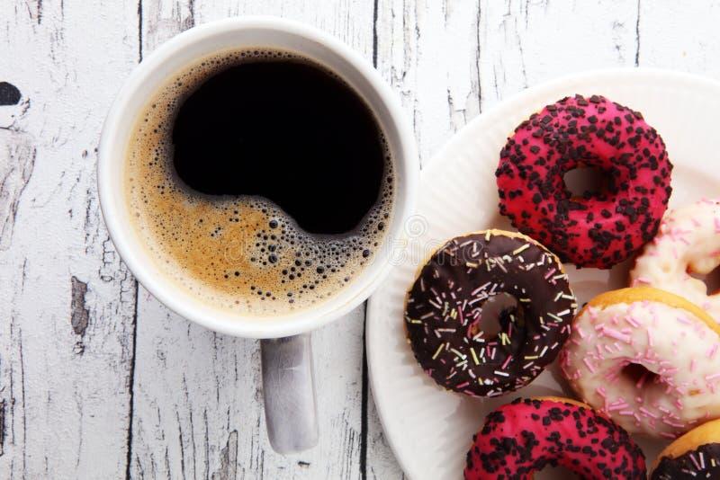 Anéis de espuma e café para um café da manhã doce no fundo de madeira fotografia de stock royalty free