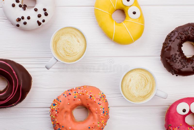 Anéis de espuma e copos de café na tabela de madeira foto de stock