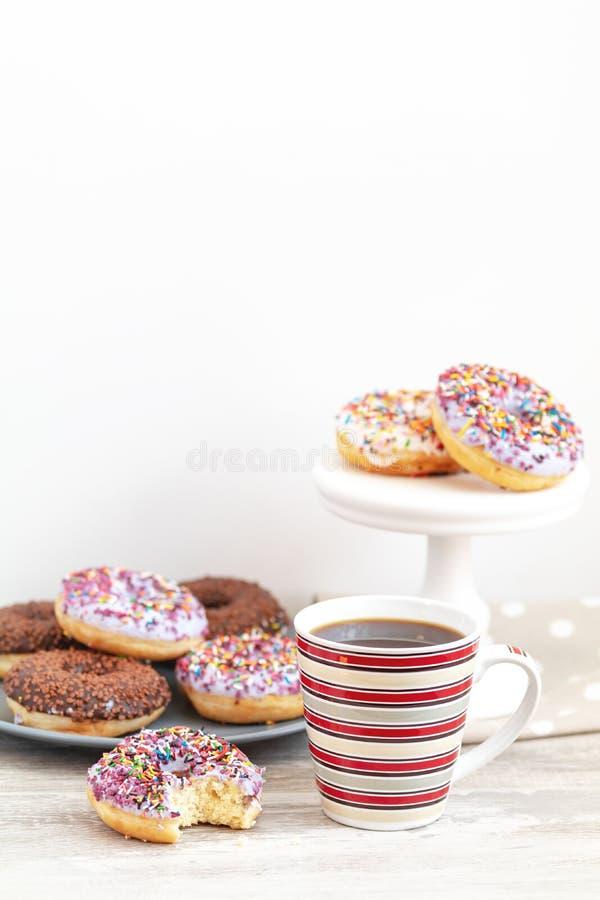 Anéis de espuma e xícara de café vitrificados deliciosos no backgr de madeira claro foto de stock royalty free