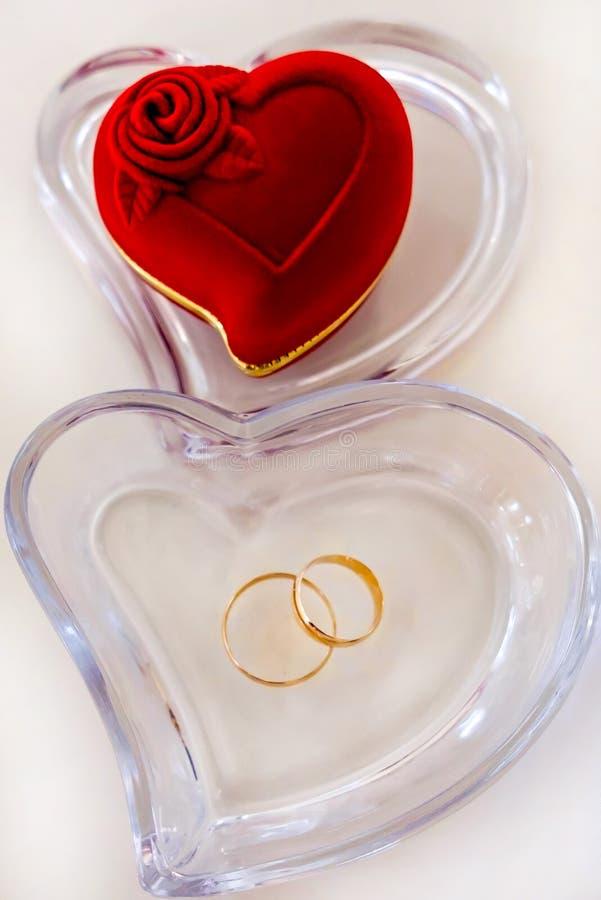 Anéis de ouro do casamento e recipiente do coração fotografia de stock royalty free