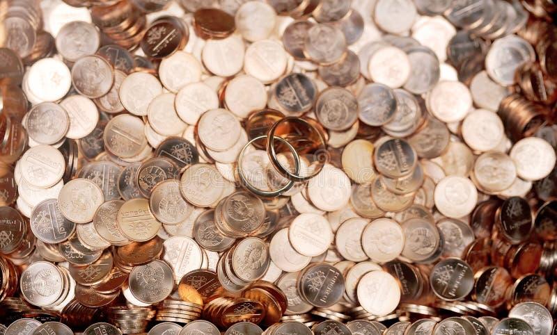 Anéis de ouro do casamento em um montão de moedas brilhantes imagens de stock royalty free