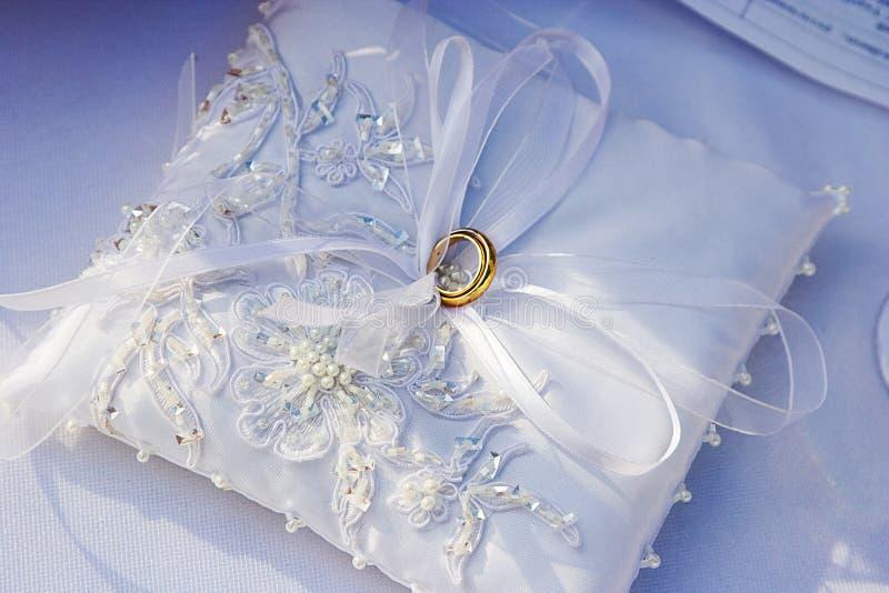 Anéis de ouro do casamento no descanso branco fotos de stock royalty free