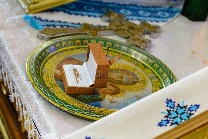 Anéis de ouro do casamento que estão em uma placa na igreja fotos de stock