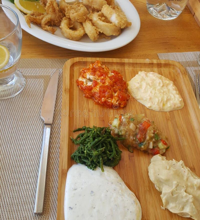 Anéis do Calamari e variedade de mergulhos na tabela do restaurante imagens de stock royalty free