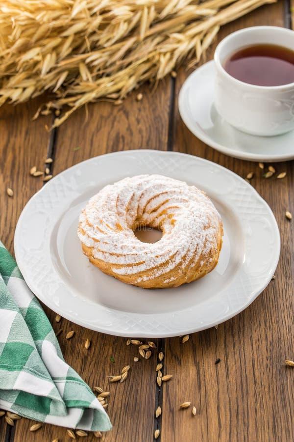 Anéis do sopro de creme com pastelaria dos choux do açúcar pulverizado na tabela de madeira imagem de stock royalty free