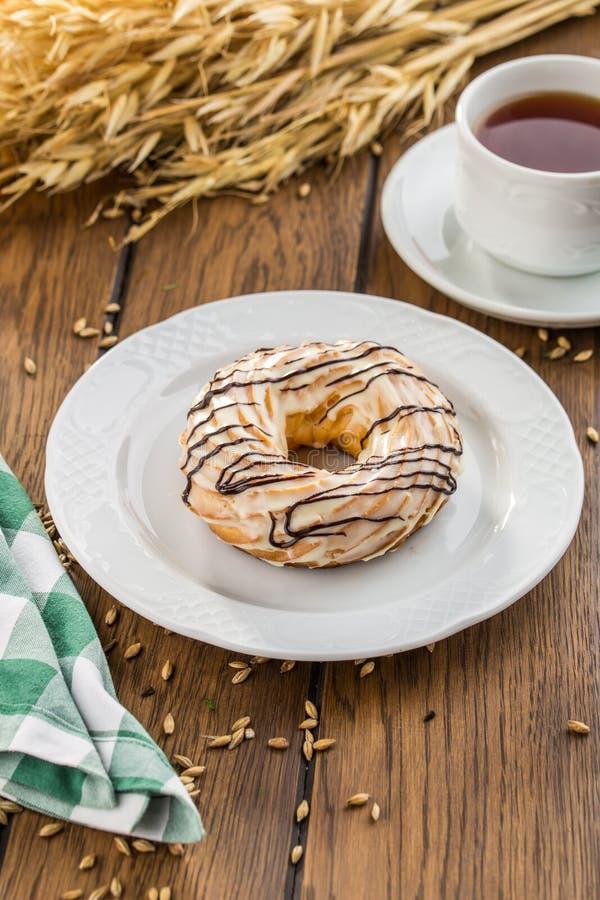 Anéis do sopro de creme com pastelaria dos choux do esmalte do chocolate na tabela de madeira imagem de stock royalty free