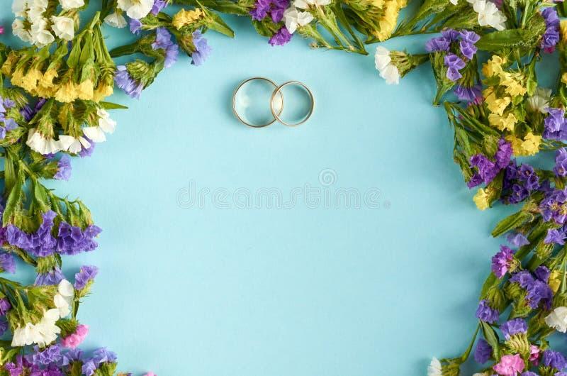Anéis dourados com as flores coloridas na composição azul do fundo, molde do casamento fotografia de stock royalty free