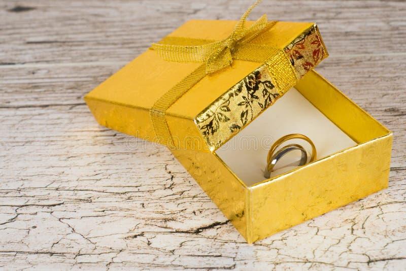 Anéis dourados e de prata dos pares na caixa de presente foto de stock royalty free
