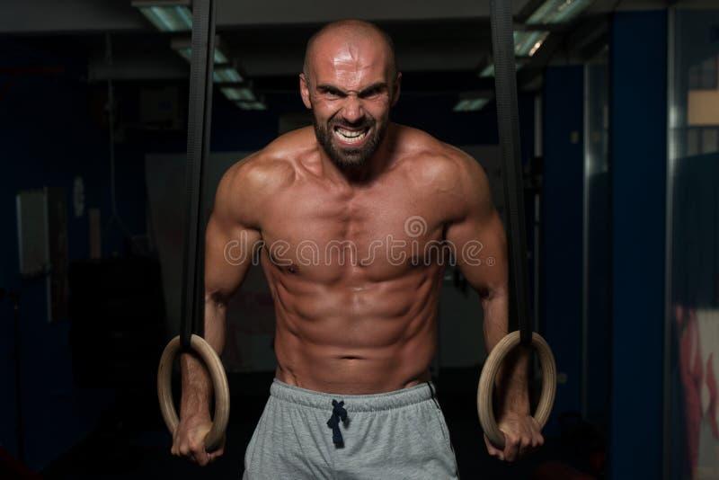 Anéis ginásticos da posse muscular do homem fotografia de stock
