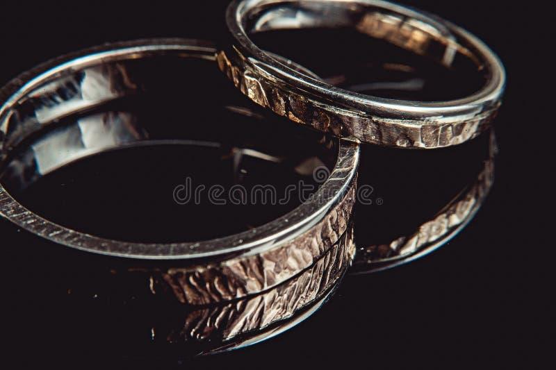 Anéis martelados do weddin no fundo preto Macro foto de stock