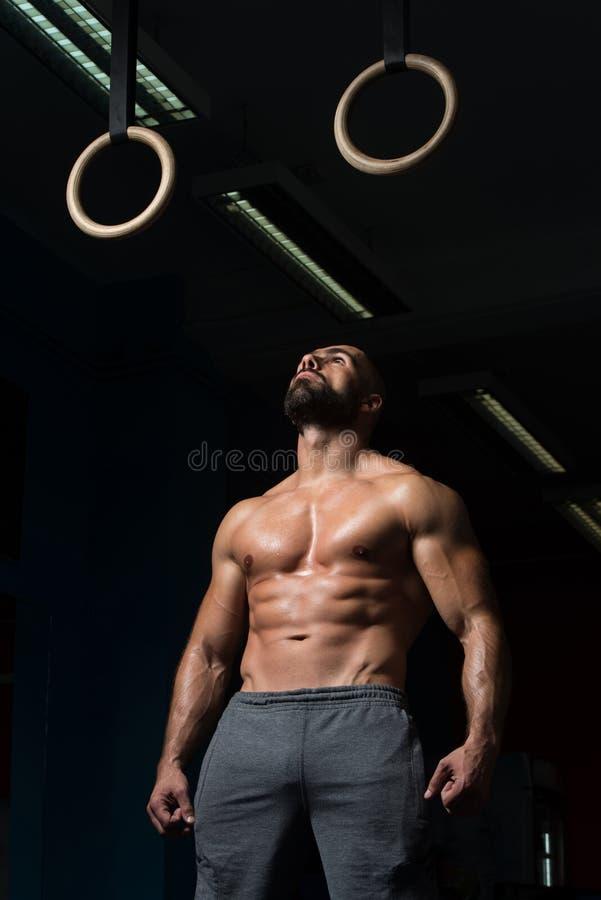 Anéis musculares de Hanging On Gymnastic do atleta imagens de stock