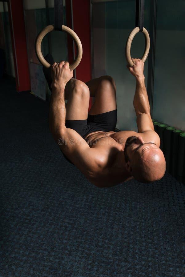 Anéis musculares de Hanging On Gymnastic do atleta fotos de stock