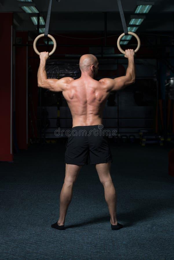 Anéis musculares de Hanging On Gymnastic do atleta fotografia de stock royalty free