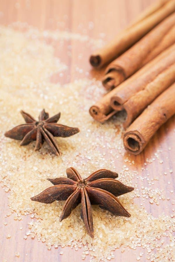 Anís de estrella y palillos de canela en el azúcar marrón fotos de archivo