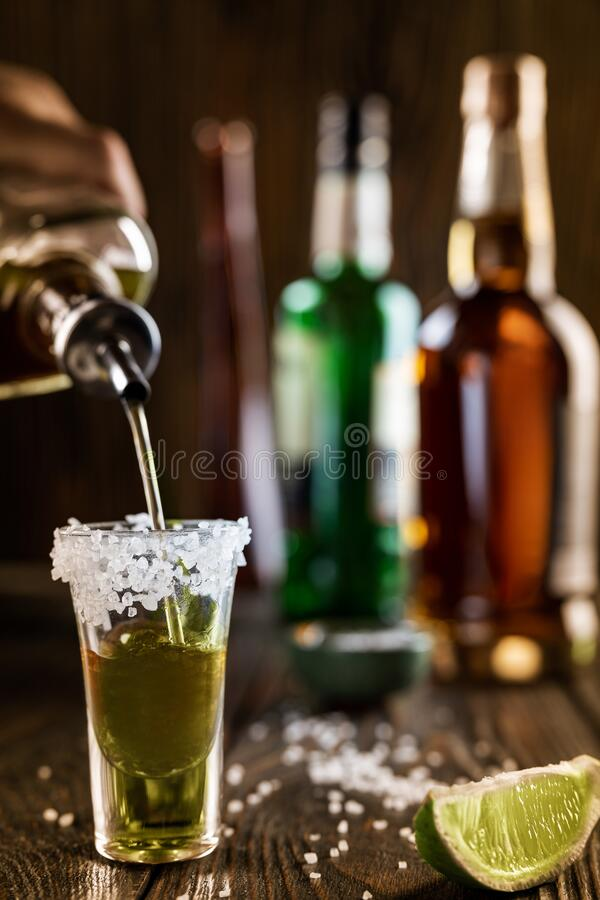 Free An Alcoholic Drink At The Bar Counter Is Poured Into A Tequila Glass With Salt At The Edges, In The Background Are Royalty Free Stock Photography - 185226277