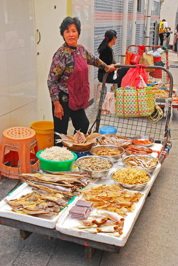 Free An Elderly Asian Lady Selling Various Types Of Dried Fish Stock Photos - 172654543